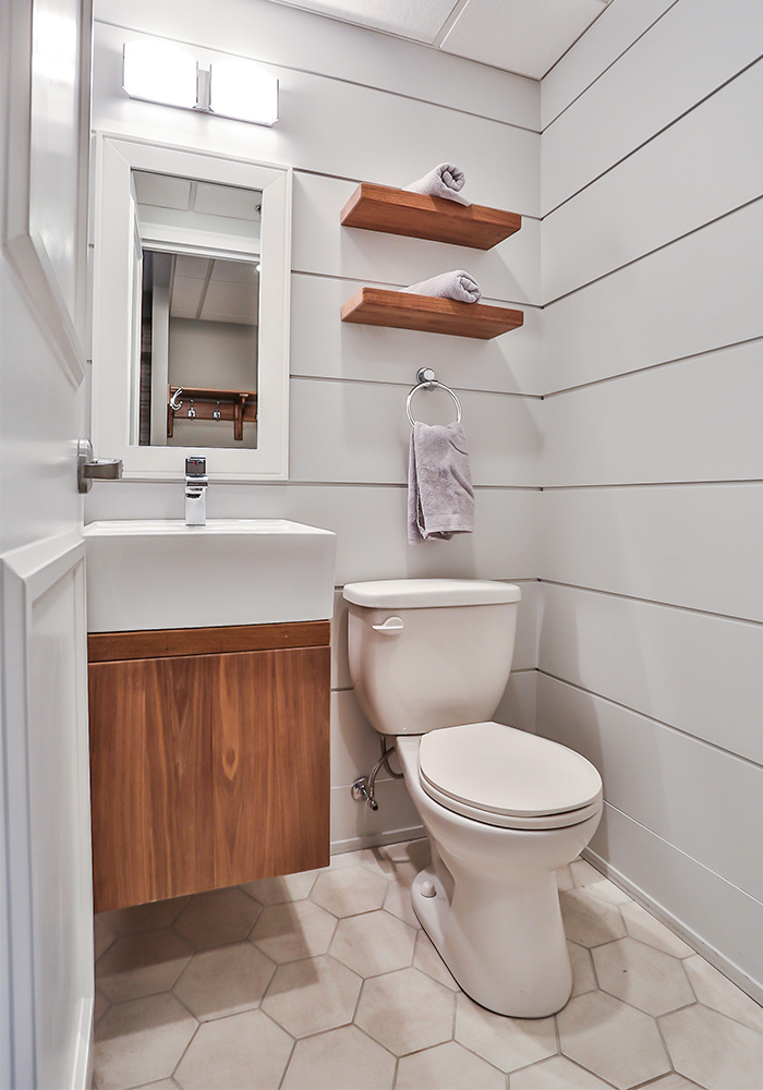 small bathroom with toilet, sink, and mirror, and wooden accent pieces
