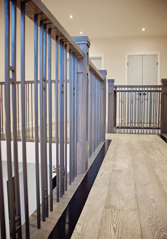 railings with metal spindles beside light coloured hardwood flooring