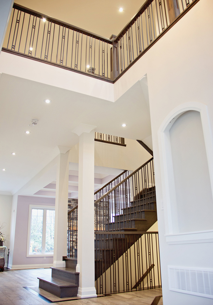entrance way with stairs, white columns, and railings with metal spindles
